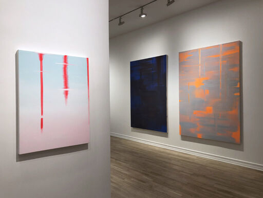 An installation view consisting of a medium-sized abstract painting with a light blue and pink gradation, a large, primarily black abstract painting revealing blue layers and brushstrokes, and a large, primarily grey abstract painting revealing orange layers and brushstrokes.
