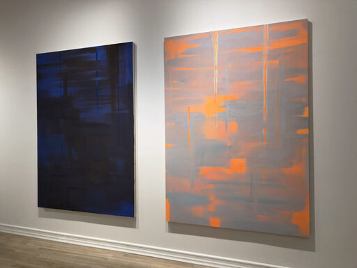An installation view consisting of a large, primarily black abstract painting revealing blue layers and brushstrokes, and a large, primarily grey abstract painting revealing orange layers and brushstrokes.