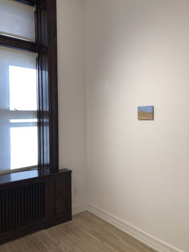 An installation view consisting of a small, contemplative Eleanor Ray painting of a desert landscape with a blue sky.