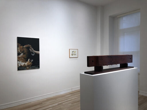 An installation view consisting of a Jesse Mockrin painting of a realistic hand clutching a dog's tail, a small H.C. Westermann drawing of a palm tree, and a rectangular wooden sculpture atop a pedestal.
