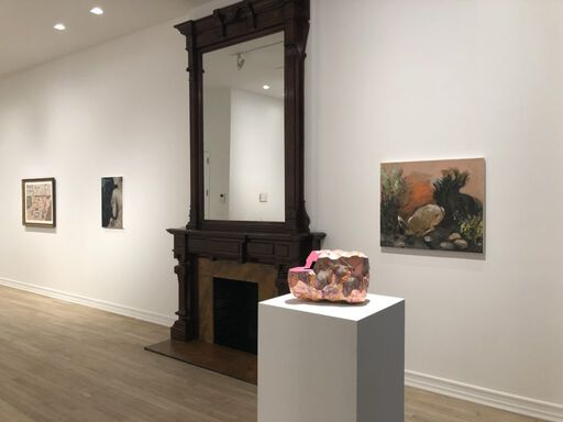 An installation view consisting of a vibrantly-painted, textured Ken Price sculpture on a pedestal, and three two-dimensional works, including a portrait of a woman clutching her body against a dark backdrop of trees, and an orange-toned landscape of a burrowing rabbit.