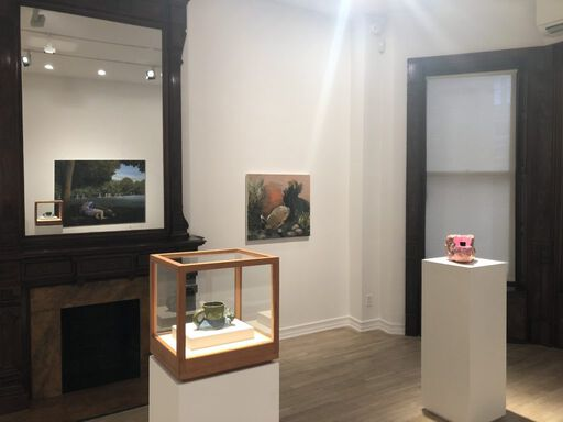 An installation view consisting of two Ken Price sculptures on individual pedestals - a green ceramic cup shaped like a snail and a vibrantly-painted, textured mass with a deep black cavity. A canvas in the background features an orange-toned landscape of a burrowing rabbit.