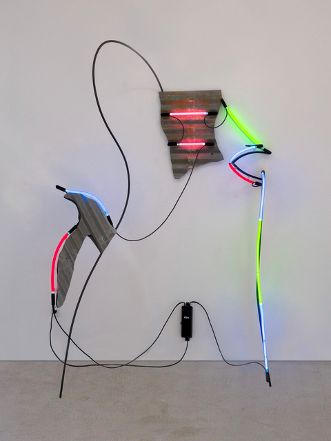 This sculpture consists of twisting and intertwining cords, metal rods, and bent pink, blue, and green neon tubes. The neon tubes are contrasted by two jagged segments of corrugated metal.