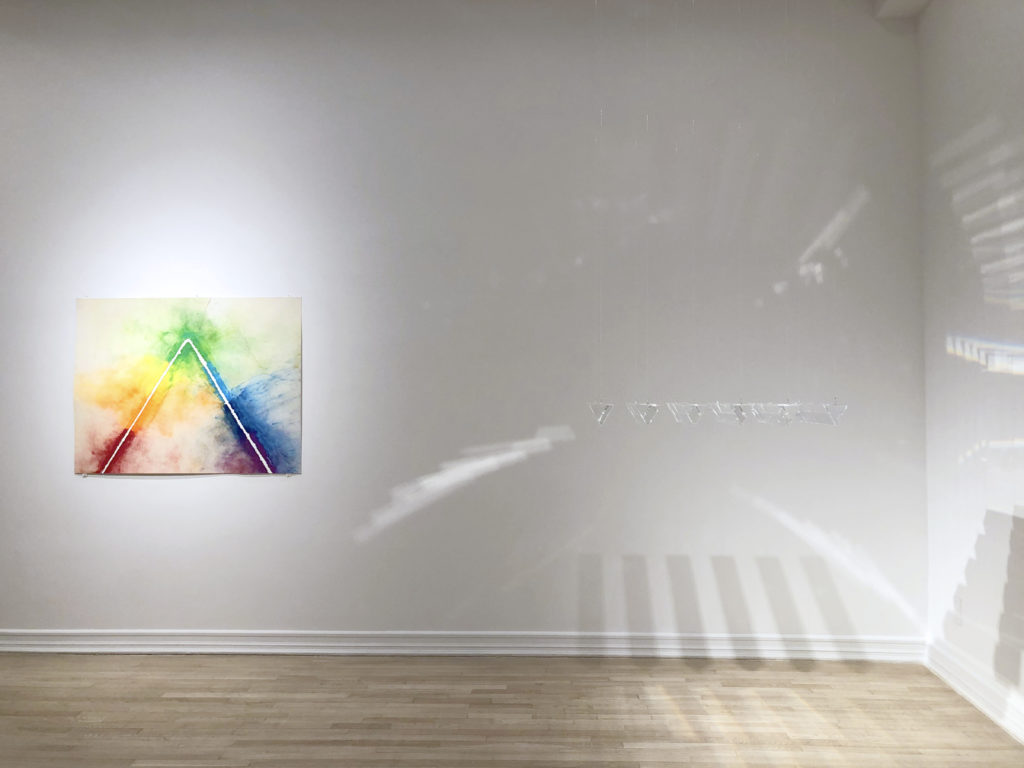 An installation view of a Charles Ross explosion drawing and suspended prism sculpture. The drawing depicts a pyramid surrounded by pigments in rainbow spectrum colors. The prisms, suspended in a row of six, reflect and disperse light onto the gallery walls.